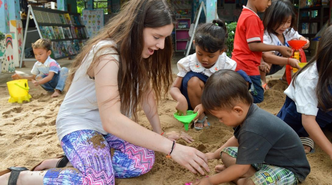 A volunteers spends time with the children in Cambodia after joining volunteering opportunities for high school students with Projects Abroad.